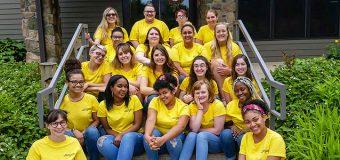 Twenty female students sitting on steps