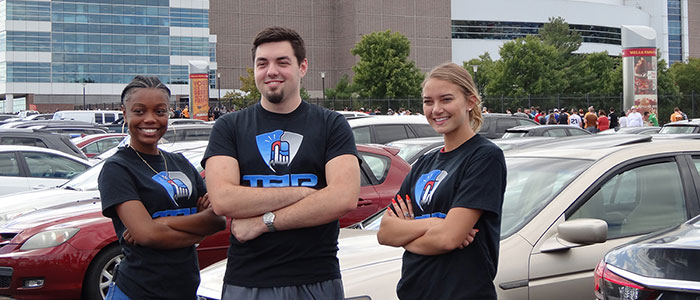 Three ESU students standing in front of the Wells Fargo Center