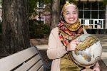 Sarah Khan sitting, pointing to Turkey on a globe