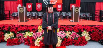 Alex Walsh stands in front of the stage of graduation day.