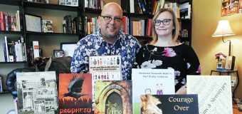 Christina Steffy poses with her husband David J. Reimer Sr. pose in front of books at their publishing company, Crave.